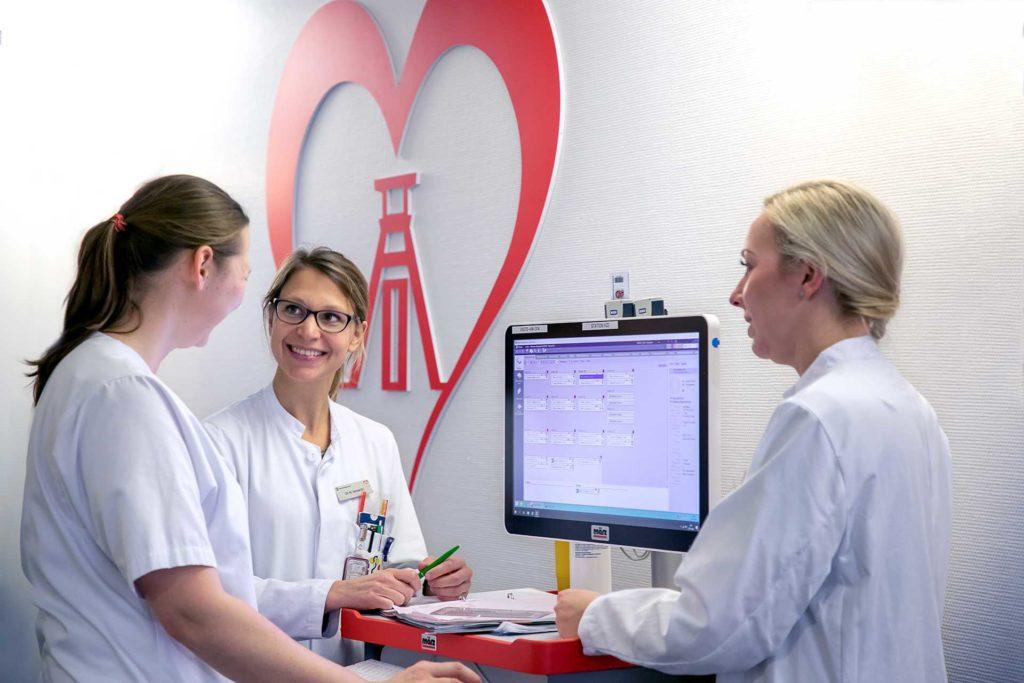 Zwei Ärztinnen und eine Krankenschwester bei der Visite.