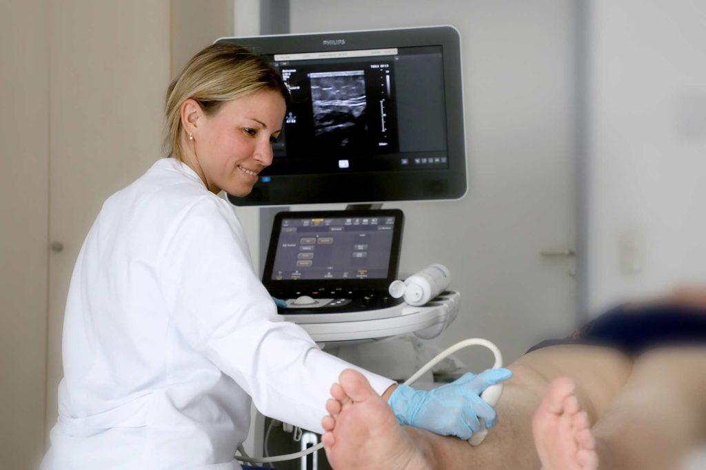 Eine Ärztin bei einer Sonografie der Beinvenen.