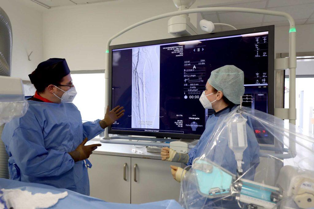 Zwei Kardiologen im OP vor einem großen Untersuchungsmonitor.